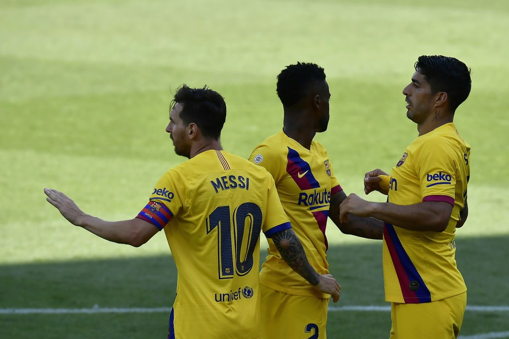 Barcelona's Nelson Semedo, center, celebrates with his teammates Lionel Messi, left, and Luis Suarez, his goal against Alaves during the Spanish La Li...