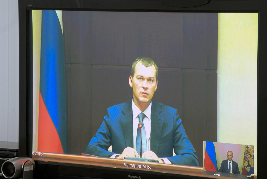 Liberal Democratic Party lawmaker Mikhail Degtyarov is seen on a TV screen during a video conference with Russian President Vladimir Putin in Kerch, C...