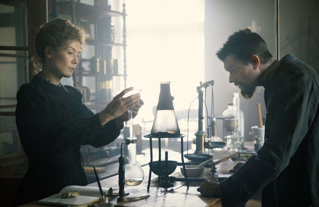 """This image released by Amazon shows Rosamund Pike as Marie Curie, left, and Sam Riley as Pierre Curie in a scene from """"Radioactive."""" (Amazon via AP)"""