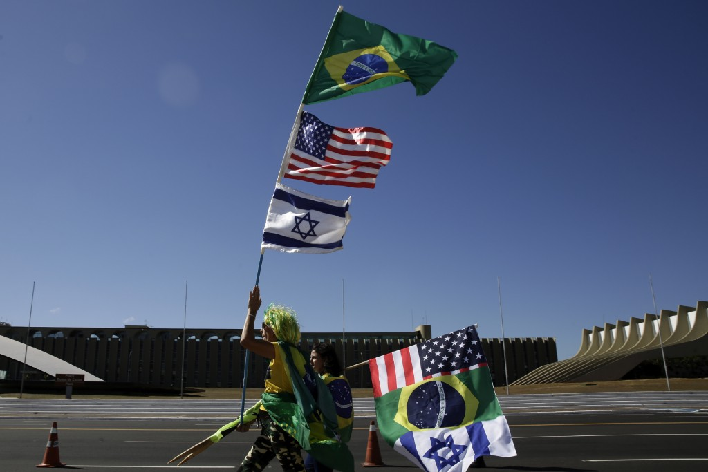 A supporter of Brazil's President Jair Bolsonaro carries the flags of Brazil, Israel, and the United States, during a pro-Bolsonaro demonstration in B...