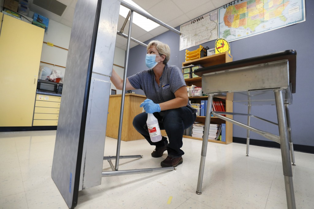 Des Moines Public Schools custodian Cynthia Adams cleans a desk in a classroom at Brubaker Elementary School, Wednesday, July 8, 2020, in Des Moines, ...