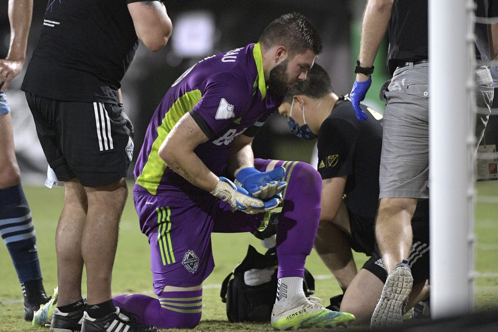 Vancouver Whitecaps goalkeeper Maxime Crepeau holds his hand after being injured on a play in front of the goal during the second half of an MLS socce...