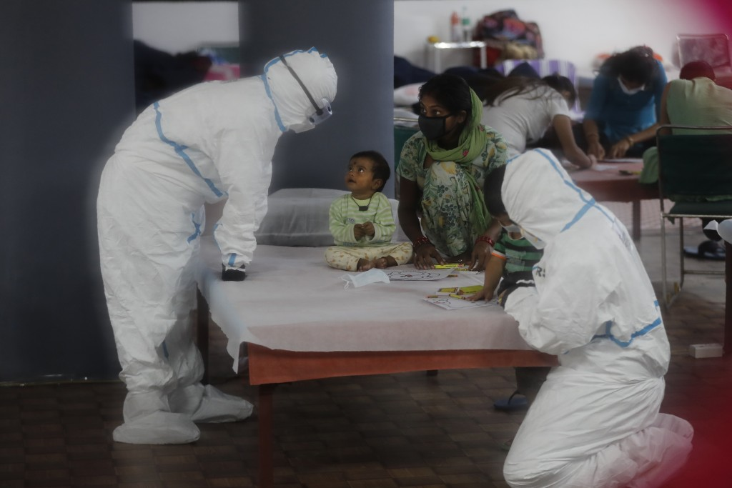 Doctors and health workers entertain children at a COVID-19 care center functioning in an indoor stadium in New Delhi, India, Monday, July 20, 2020. (...