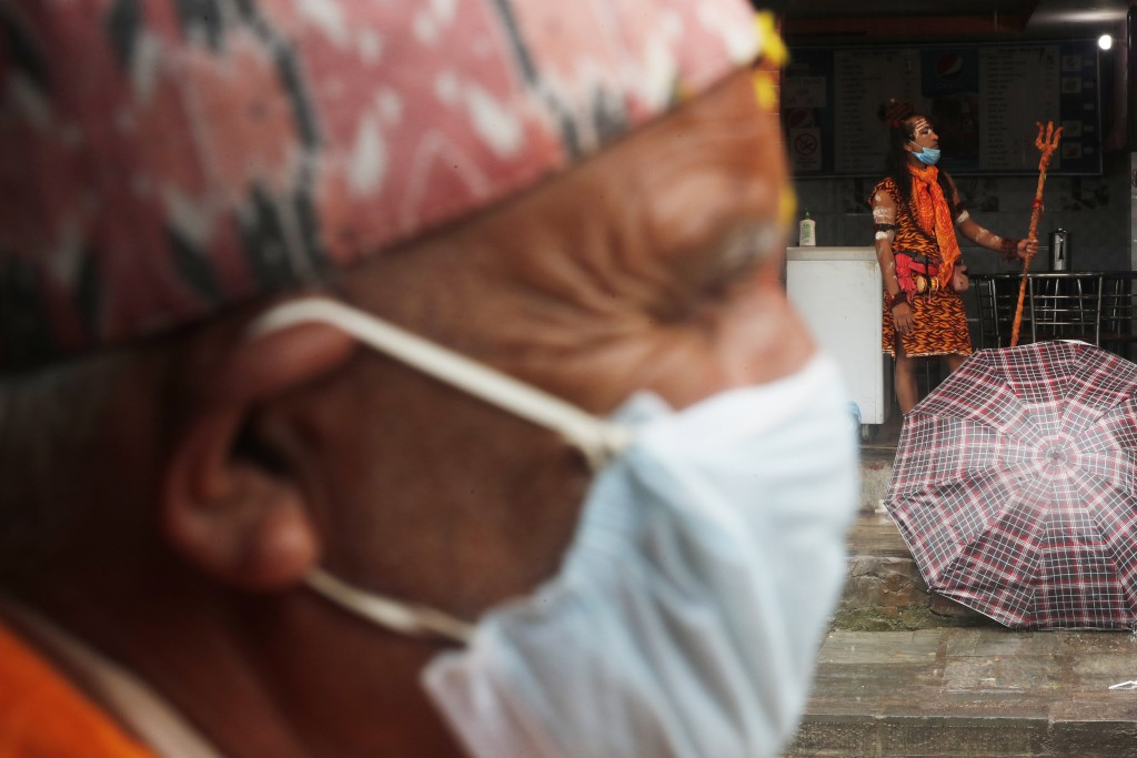 A man stands dressed as Hindu god Shiva to attract alms as a Nepalese Hindu devotee wearing mask offers prayers from outside the closed gate of Pashup...