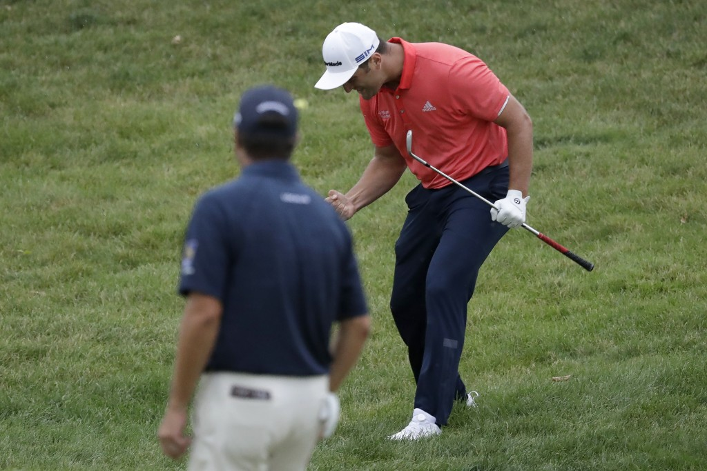 Jon Rahm, of Spain, right, celebrates after chipping for birdie on the 16th hole as Ryan Palmer watches during the final round of the Memorial golf to...