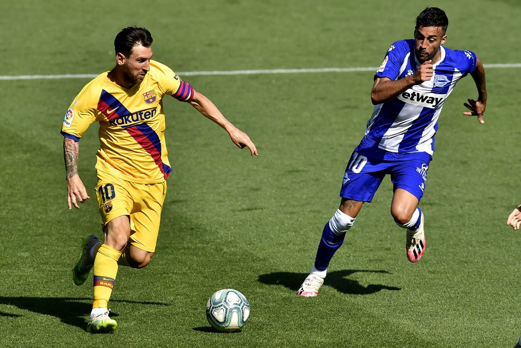 Barcelona's Lionel Messi, left, fights for the ball with Alaves' Victor Camarasa during the Spanish La Liga soccer match between Alaves and FC Barcelo...