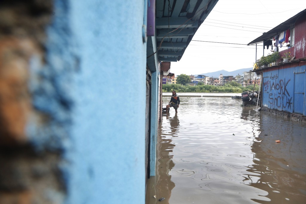A Nepalese man stands outside his flooded house on the bank of Bagmati river following heavy monsoon rains in Kathmandu, Nepal, Monday, July 20, 2020....