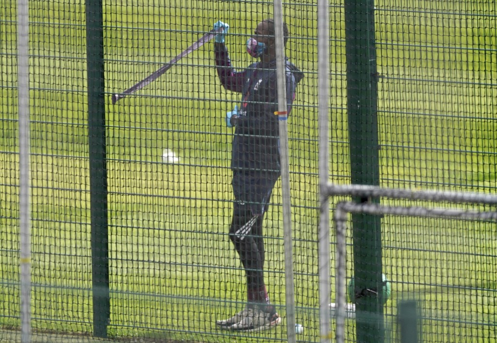 England's Jofra Archer wearing face mask and gloves as a precaution against the coronavirus trains in the nets at Old Trafford in Manchester, England,...