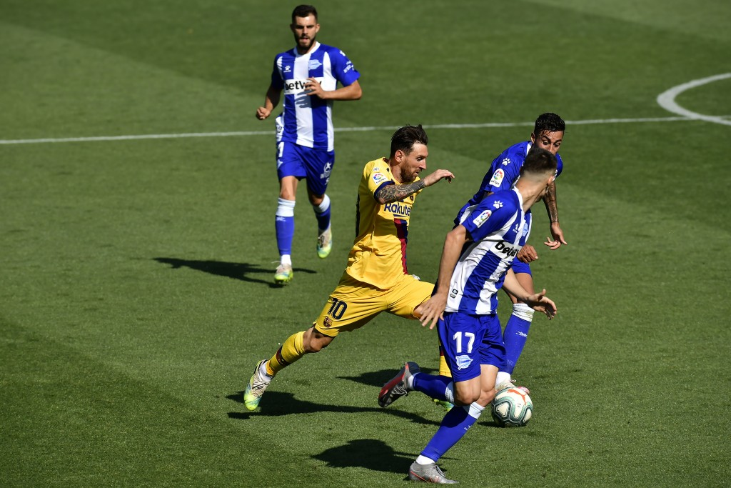 Barcelona's Lionel Messi fights for the ball with Alaves' Adrian Marin, front, during the Spanish La Liga soccer match between Alaves and FC Barcelona...