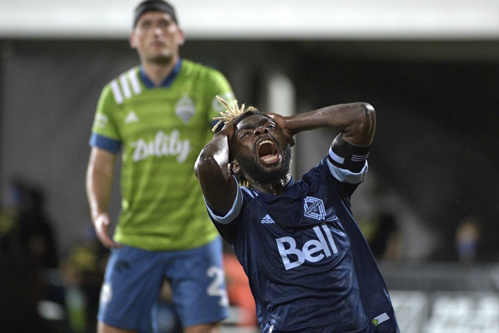 Vancouver Whitecaps midfielder Leonard Owusu reacts after missing a shot on goal as Seattle Sounders defender Shane O'Neill, left, watches during the ...