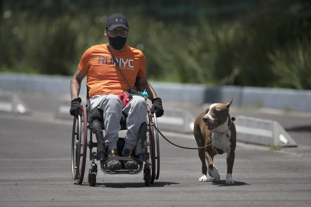 A man wearing a mask to curb the spread of the new coronavirus and riding a wheelchair exercises with his dog in Chapultepec Park, Mexico City, Sunday...