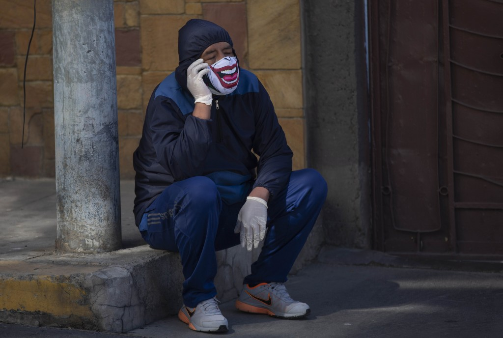 A man wearing a mask speaks on his mobile phone as waits to be tested during a house-to-house new coronavirus testing drive, in the Villa San Luis nei...