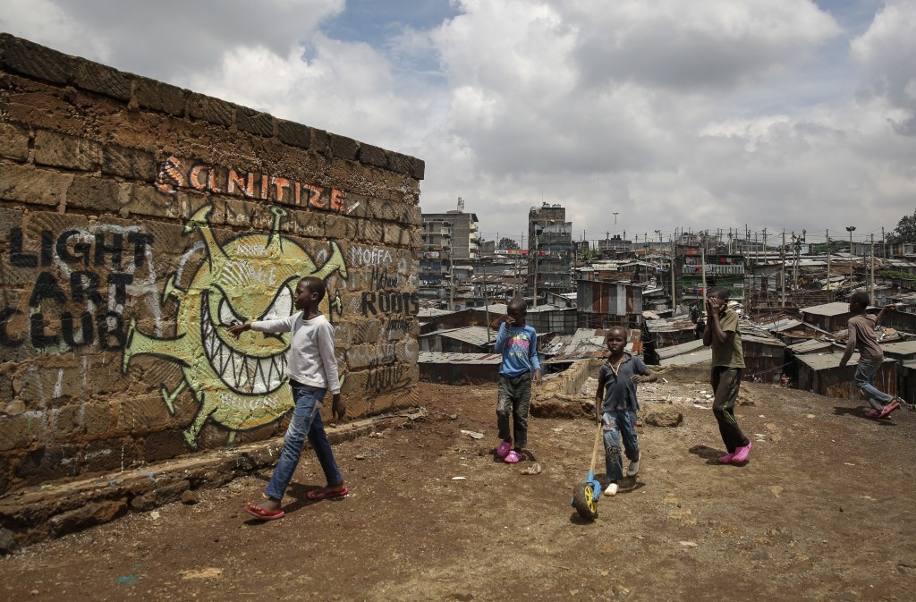 FILE - In this April 22, 2020, file photo, children walk past an informational mural depicting the coronavirus and warning people to sanitize to preve...