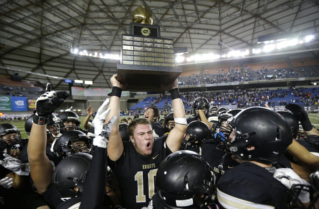 FILE - In this Dec. 3, 2016 file photo, Royal quarterback Kaden Jenks (10) celebrates with the trophy after Royal beat Connell in the Washington Div. ...