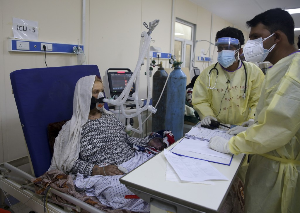 Afghan doctors help a patient to breathe through an oxygen mask in the Intensive Care Unit ward for COVID-19 patients at the Afghan-Japan Communicable...