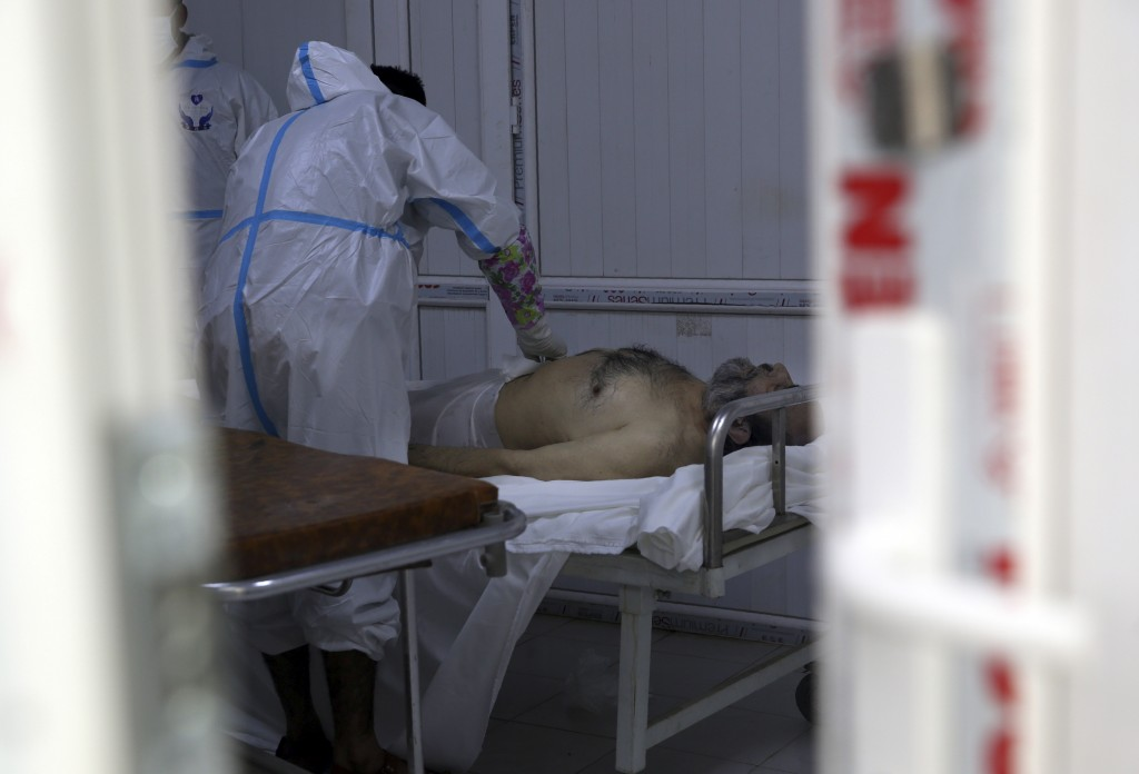 Afghan health workers wrap in a funeral shroud a man who died of COVID-19 at the Afghan-Japan Communicable Disease Hospital in Kabul, Afghanistan, Tue...