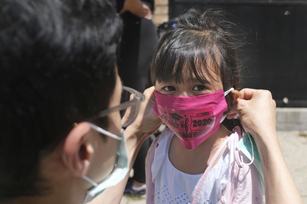 FILE - In this June 10, 2020, file photo, Olivia Chan's father helps her with a new mask she received during a graduation ceremony for her Pre-K class...