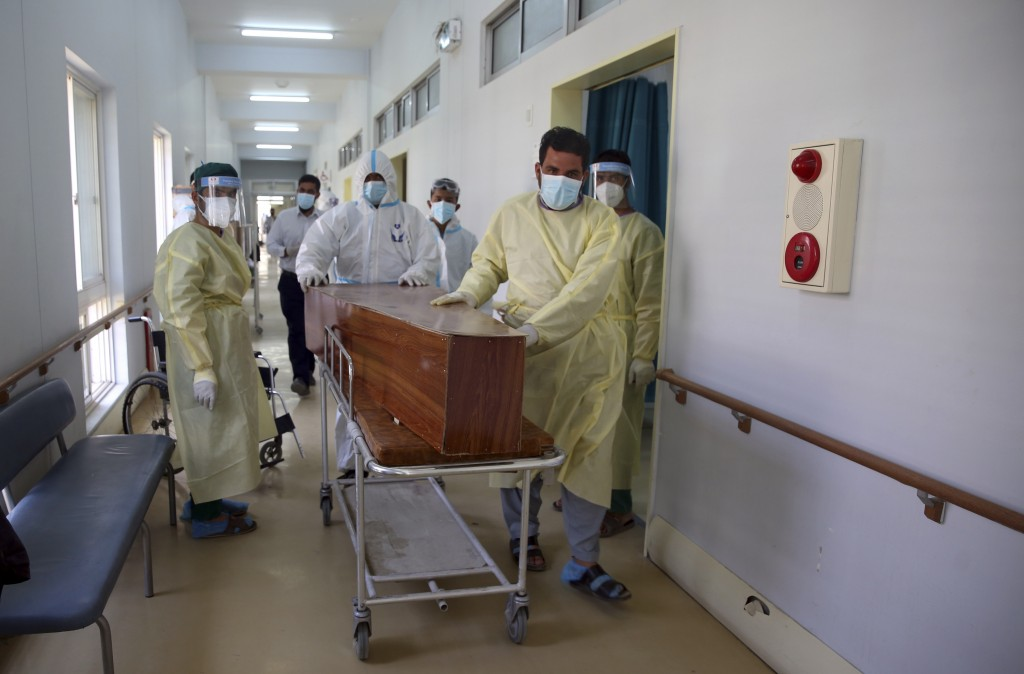 Afghan health workers carry the body of a man who died from COVID-19 at the Afghan-Japan Communicable Disease Hospital in Kabul, Afghanistan, Tuesday ...