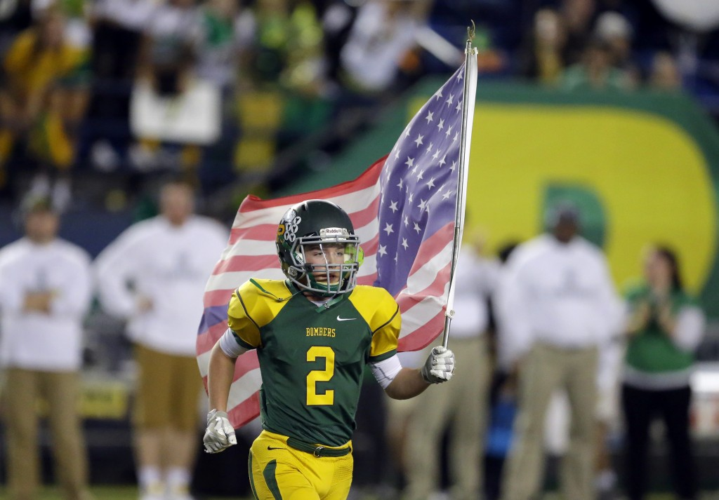 FILE - In this Dec. 3, 2016 file photo, Richland's Ryan Kriskovich runs out with the U.S. flag at the start of the Washington Div. 4A high school foot...