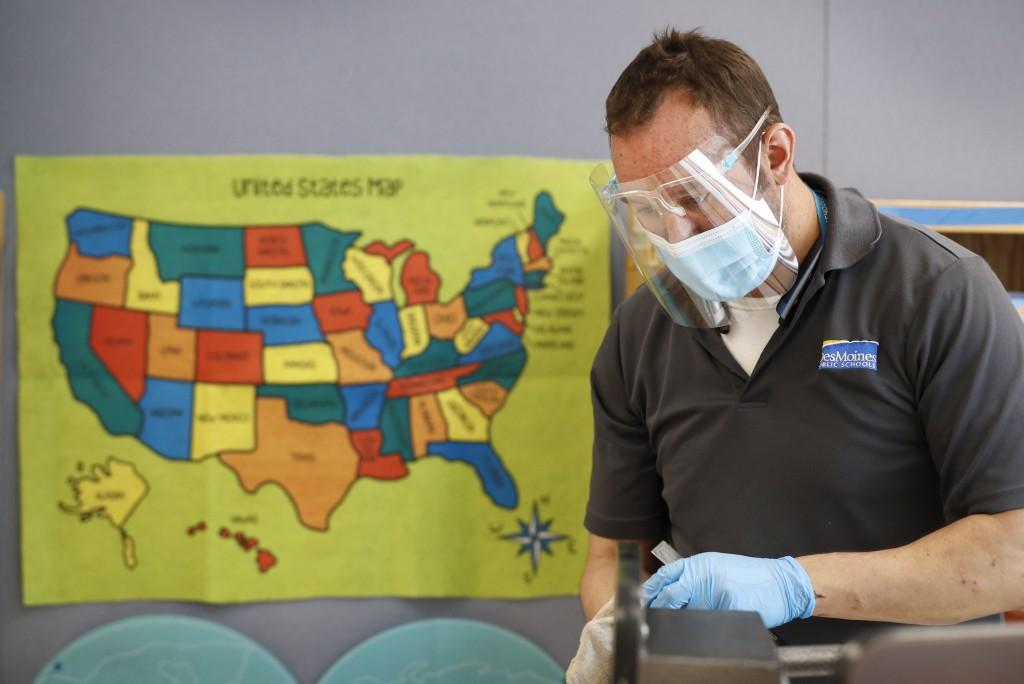 Des Moines Public Schools custodian Joel Cruz cleans a desk in a classroom at Brubaker Elementary School, Wednesday, July 8, 2020, in Des Moines, Iowa...