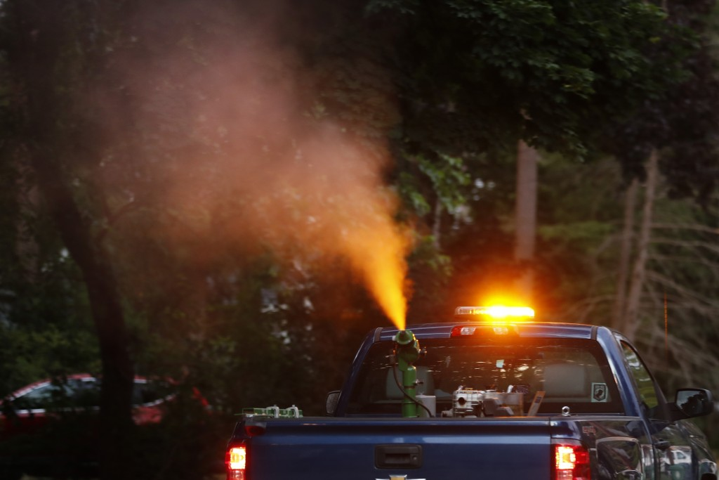 A crew from the East Middlesex Mosquito Control Project spray to control mosquitos from a pick-up truck on Wednesday, July 8, 2020, while driving thro...