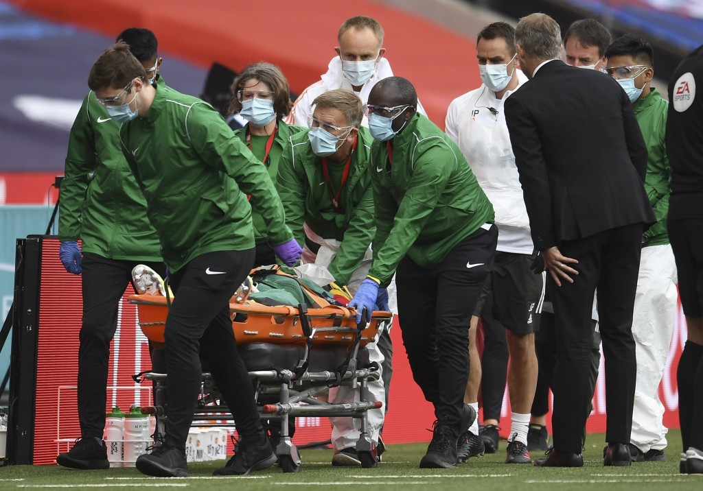 Manchester United's Eric Bailly is taken from the field after a clash of heads during the English FA Cup semifinal soccer match between Chelsea and Ma...
