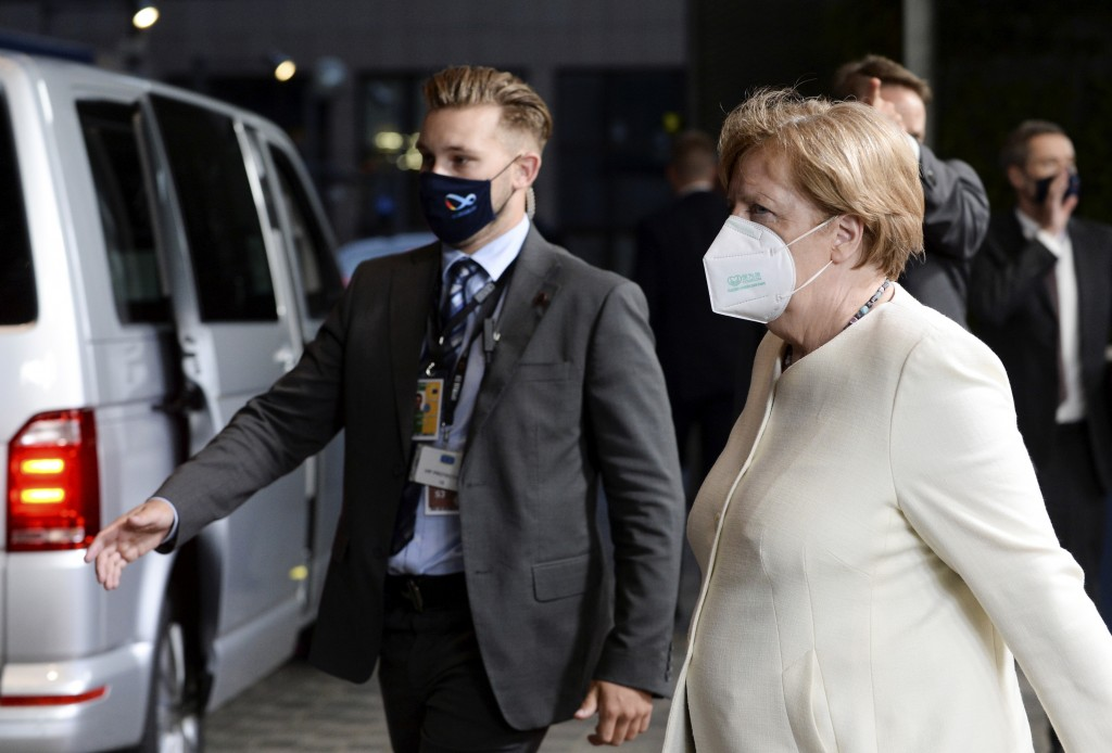 German Chancellor Angela Merkel, right, leaves the EU Council building early in the morning during an EU summit in Brussels, Monday, July 20, 2020. Le...