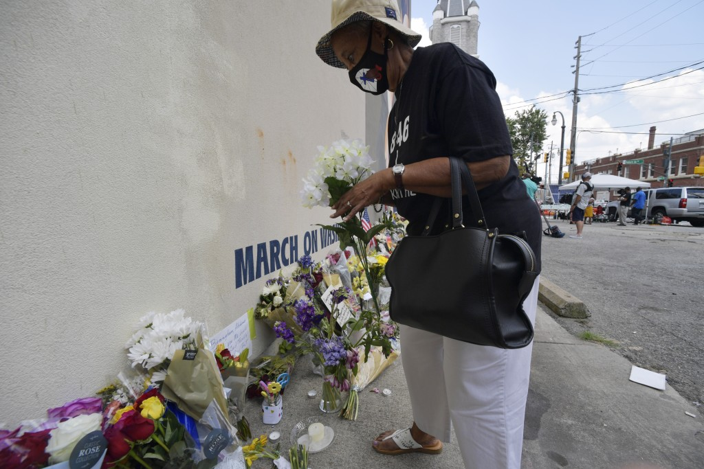 A woman lays flowers down at a make-shift memorial near the home of Rep. John Lewis, D-Ga., Sunday, July 19, 2020, in Atlanta. Lewis, who died Friday ...