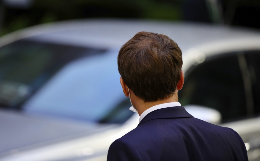 French President Emmanuel Macron waits for his car as he leaves the European Council building in the early morning during an EU summit in Brussels, Mo...