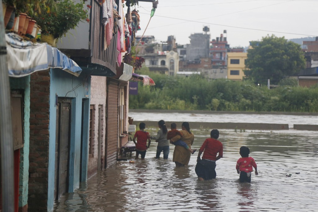 Nepalese people walk towards their flooded houses on the bank of the Bagmati river after water levels receded in Kathmandu,  Nepal, Monday, July 20, 2...