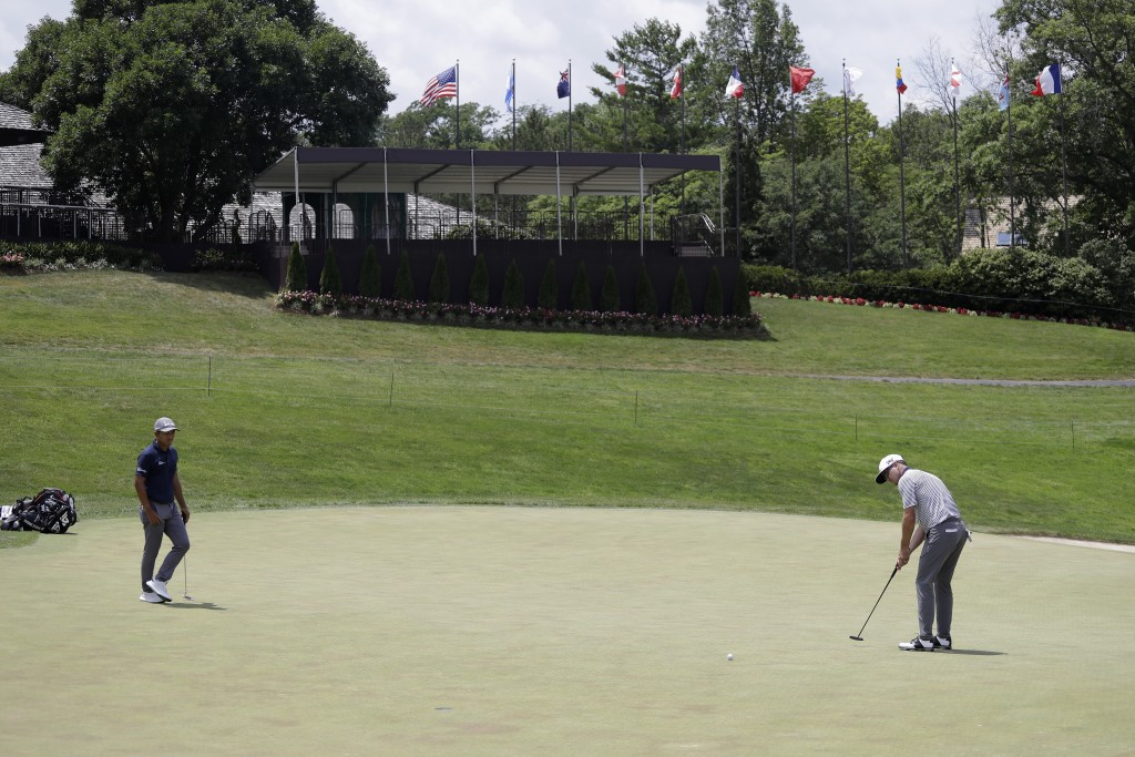 Zach Johnson, right, putts on the 18th green next to C. T. Pan, of Taipei, during the final round of the Memorial golf tournament, Sunday, July 19, 20...