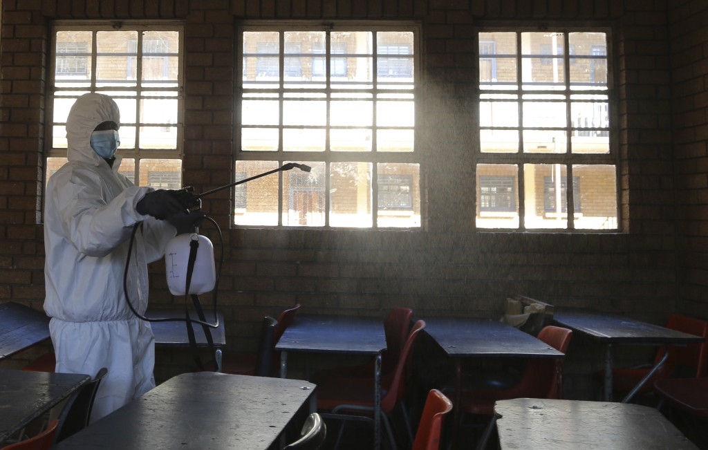 FILE - In this May 26, 2020, file photo, a worker from Bidvest Prestige wearing personal protective equipment, sprays disinfectant in a classroom to h...