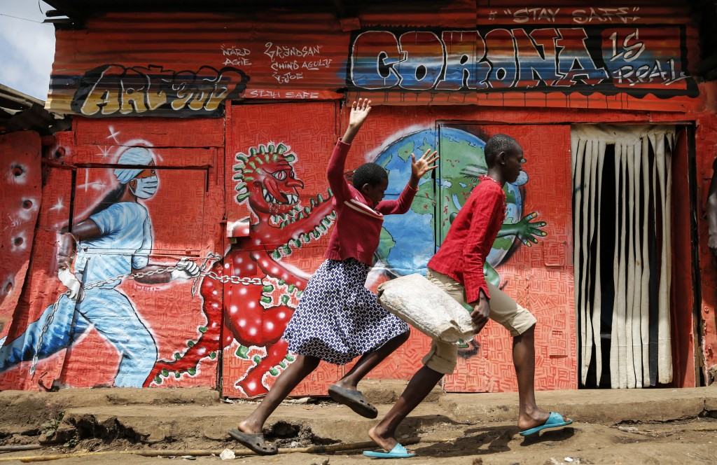 FILE - In this June 3, 2020, file photo, children run down a street past an informational mural warning people about the dangers of the new coronaviru...