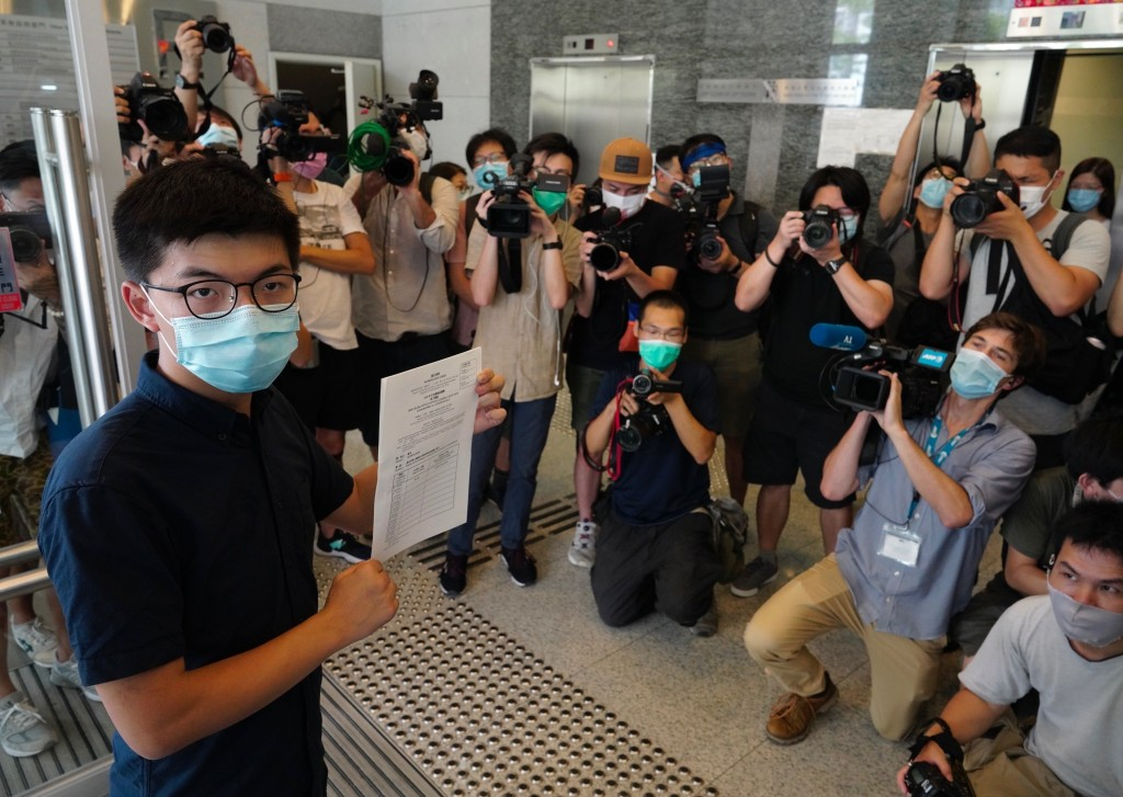 Hong Kong pro-democracy activist Joshua Wong poses for a picture with the nomination papers as he files his candidacy in Legislative Council elections...