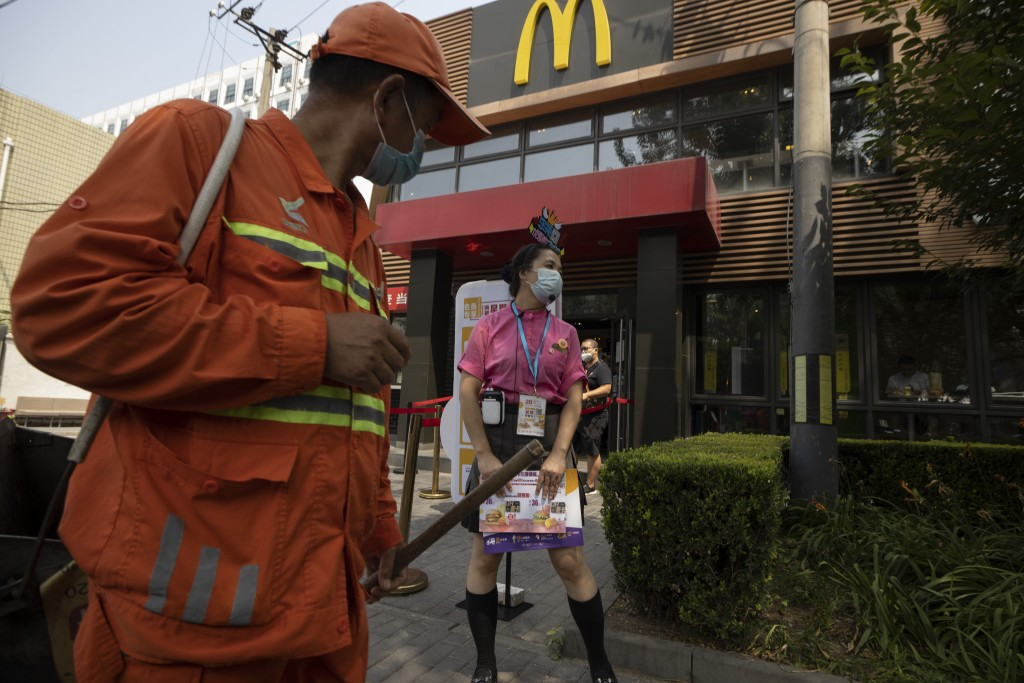A worker wearing mask to curb the spread of the coronavirus waits to guide visitors to a McDonald's fast-food restaurant in Beijing on Monday, July 20...