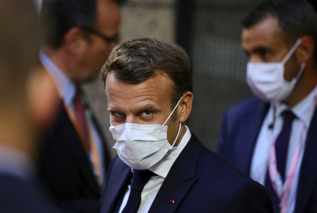 French President Emmanuel Macron, center, leaves the European Council building in the early morning during an EU summit in Brussels, Monday, July 20, ...