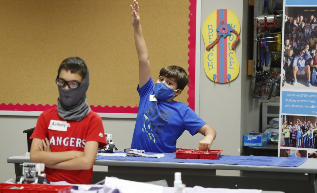 FILE - In this July 14, 2020, file photo, amid concerns of the spread of COVID-19, Aiden Trabucco, right, wears a mask as he raises his hand to answer...