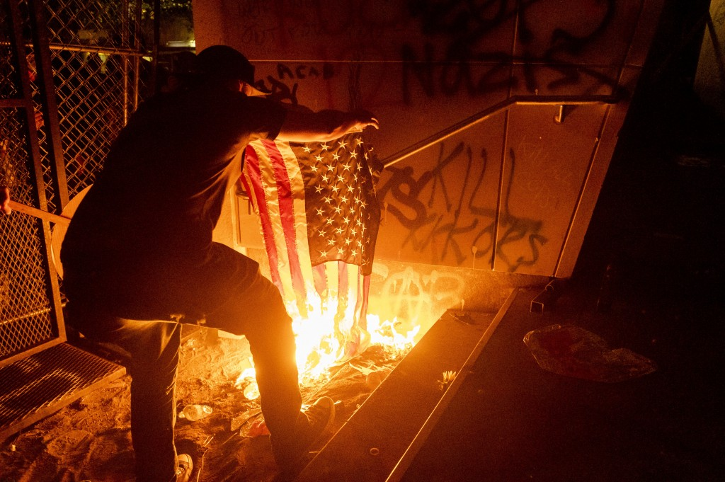 A Black Lives Matter protester burns an American flag outside the Mark O. Hatfield United States Courthouse on Monday, July 20, 2020, in Portland, Ore...