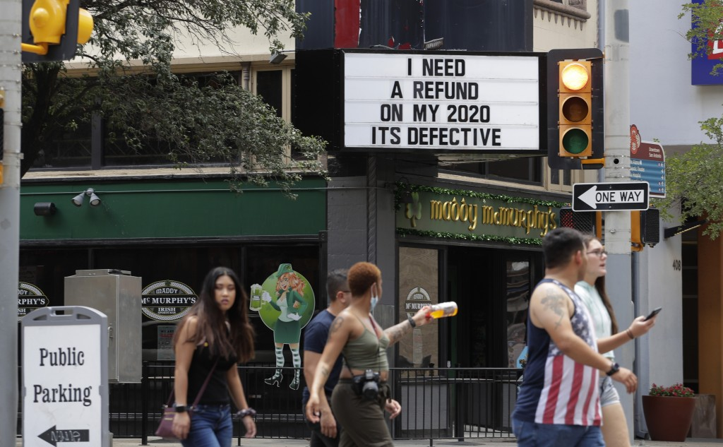 Visitors, some wearing masks to protect against COVID-19, walk through downtown San Antonio, Monday, July 20, 2020. Cases of COVID-19 continue to spik...