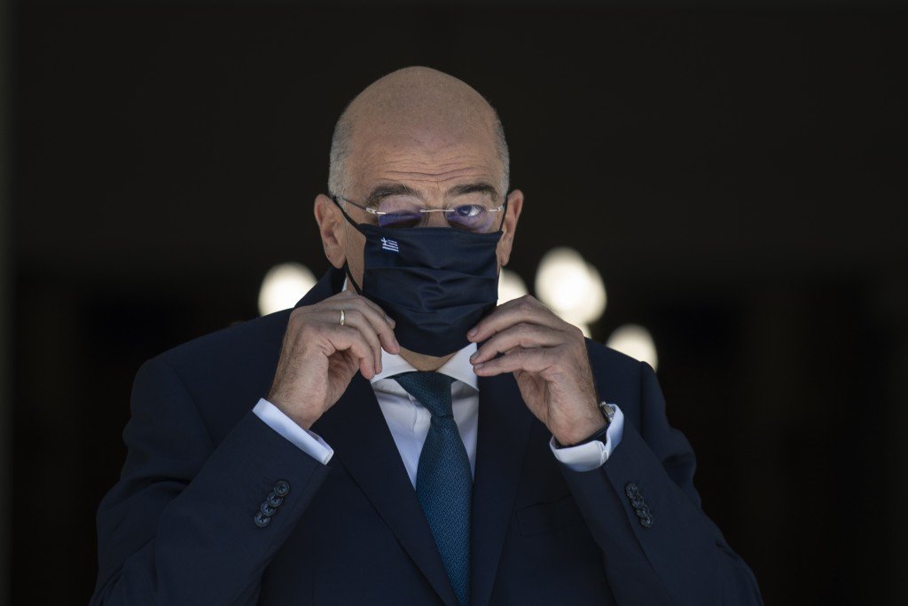 Greek Foreign Minister Nikos Dendias, adjusts his mask during the arrival of his German counterpart Heiko Maas before their meeting in Athens, on Tues...