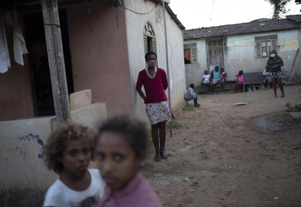 """A woman stands in front of her home as donated food and kits of cleaning products and protective face masks are distributed at the Maria Joaquina """"Qui..."""