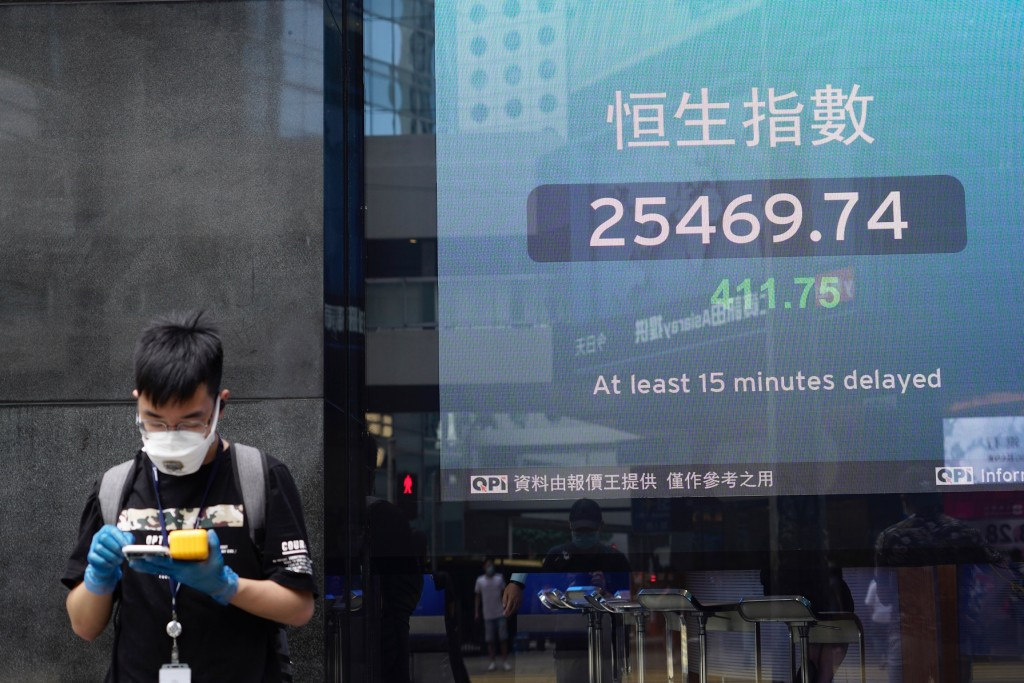A man wearing a face mask stands next to a bank's electronic board showing the Hong Kong share index in Hong Kong Tuesday, July 21, 2020. Asian shares...