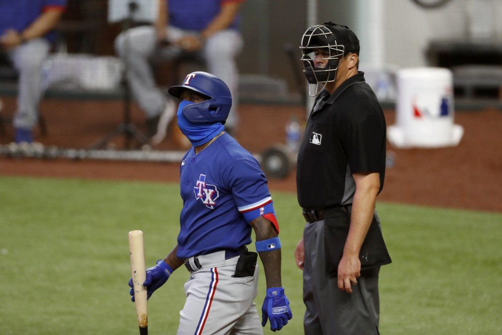 Texas Rangers outfielder Adolis Garcia, left, wears a face covering as he walks past umpire Mike DiMuro on his way to the plate to bat during an intra...