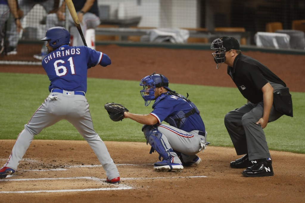 Umpire Mike DiMuro, right, crouches behind Texas Rangers catcher Jeff Mathis, center, as Robinson Chirinos (61) waits for a pitch during an intrasquad...