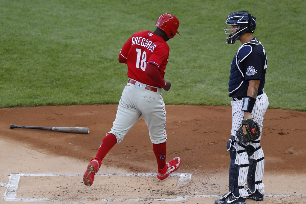 Philadelphia Phillies Didi Gregorius (18) trots past New York Yankees catcher Gary Sanchez as he scores on J.T. Realmuto's first-inning, RBI double in...