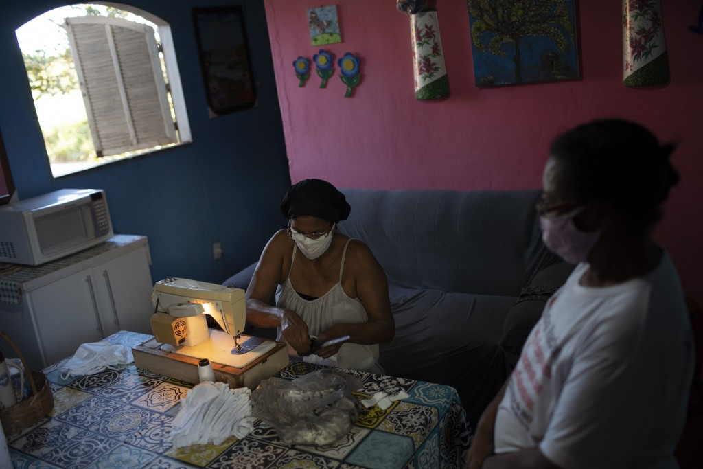 """Rosane Da Franca, left, sews protective face masks at her home at the Maria Joaquina """"Quilombo"""" in Cabo Frio, on the outskirts of Rio de Janiero, Braz..."""