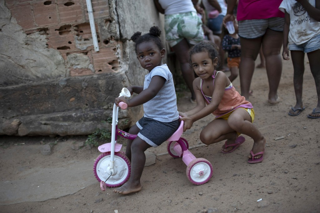 Children play as the adults collect donated food, kits of cleaning products, and protective face masks amid the new coronavirus pandemic, at the Maria...