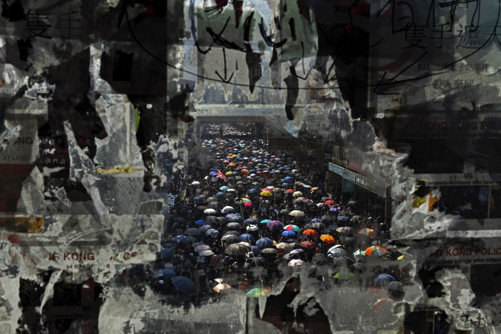 FILE - In this Oct. 1, 2019, file photo, marching anti-government protesters are seen through a glass with peeled off posters in Hong Kong. With Brita...
