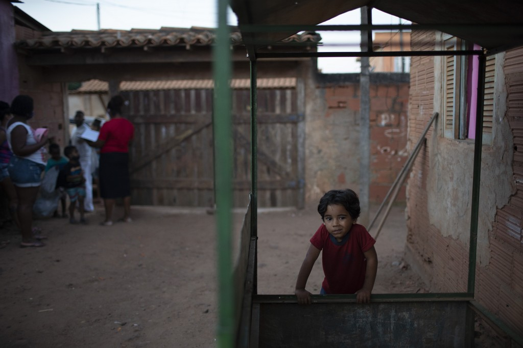A boy leans on an empty kiosk as donated food, kits of cleaning products and protective face masks are distributed amid the new coronavirus pandemic, ...