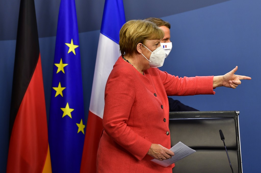 German Chancellor Angela Merkel, left, and French President Emmanuel Macron walk onto the podium prior to a media conference at the end of an EU summi...
